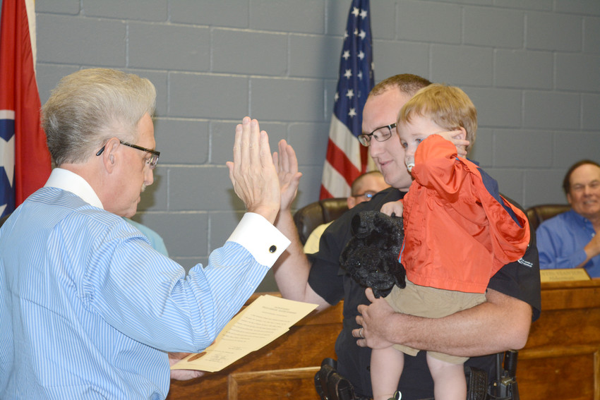 Putnam County Clerk Wayne Nabors, left, swears in new part-time Baxter Police Officer Tory Womack with his son, Oakley.