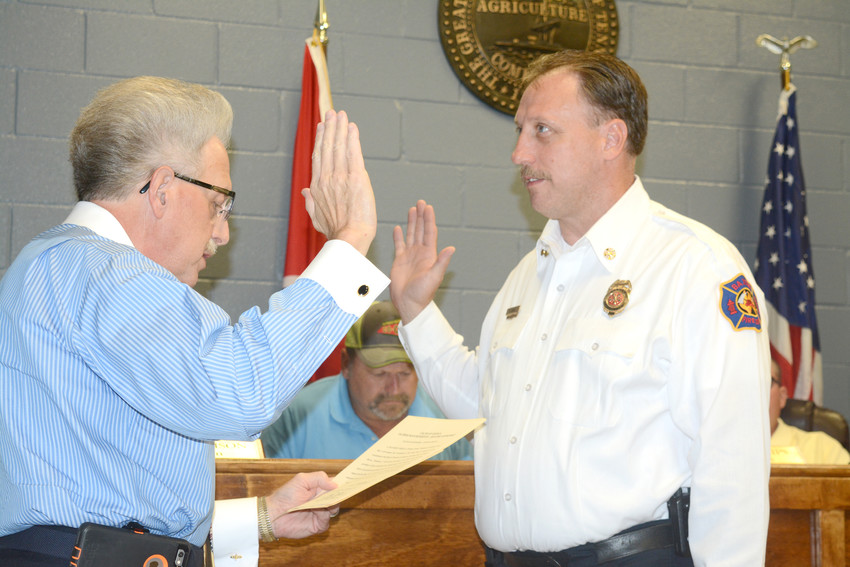 Putnam County Clerk Wayne Nabors, left, swears in Matt White as a new Baxter Police Department reserve officer. White is also the Baxter Fire Department Chief and hopes his new position on police department allows him to become Baxter's arson investigator.