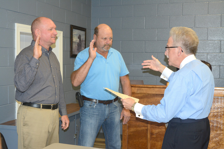Aldermen Willie Allison, left, and Greg Phillips were sworn in by Putnam County Clerk Wayne Nabors, far right, at the Baxter Board of Aldermen at their meeting Thursday evening.