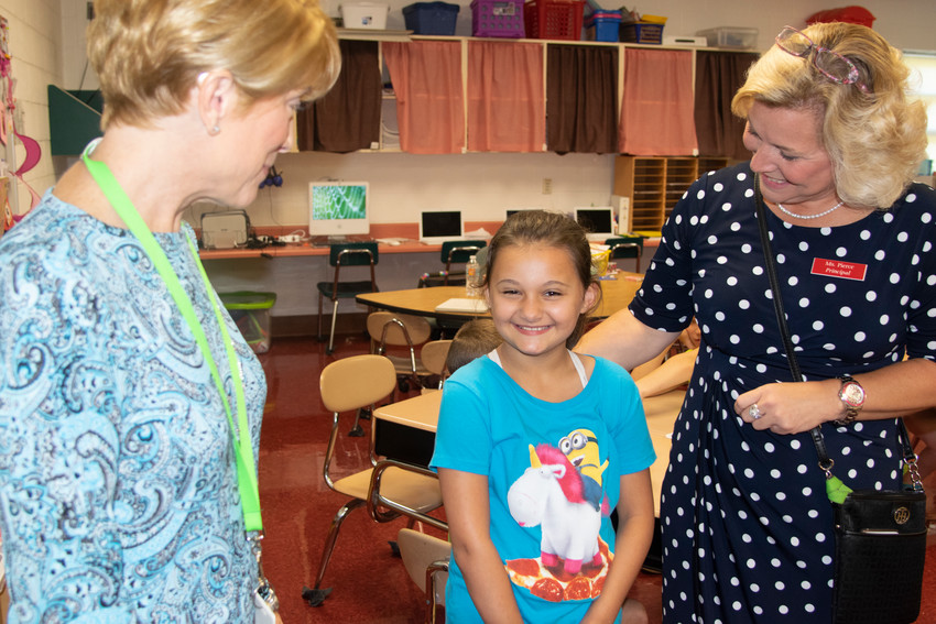 "Putnam Schools PreK-4th Supervisor of Curriculum and Instruction Jill Ramsey, left, and Cane Creek Elementary School Principal Emily Pierce, right, congratulate third grade student Kadence Brown for having the winning entry in the ""Name that Bus"" contest."