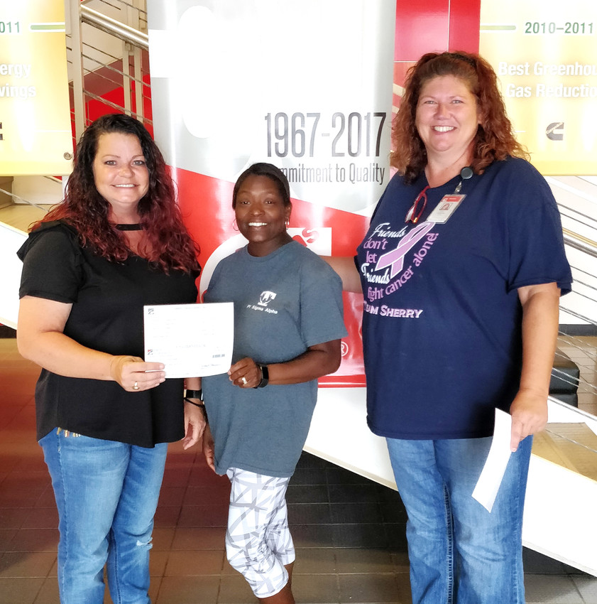 Cummins Filtration sold Cummins-branded T-shirts at the Putnam county fair so proceeds could be donated to non-profit organizations. Genesis House representatives Denise Dillon, left, and Shavonda Jones recently accepted a $1,000 check from Cummins' Kerry Perrin.