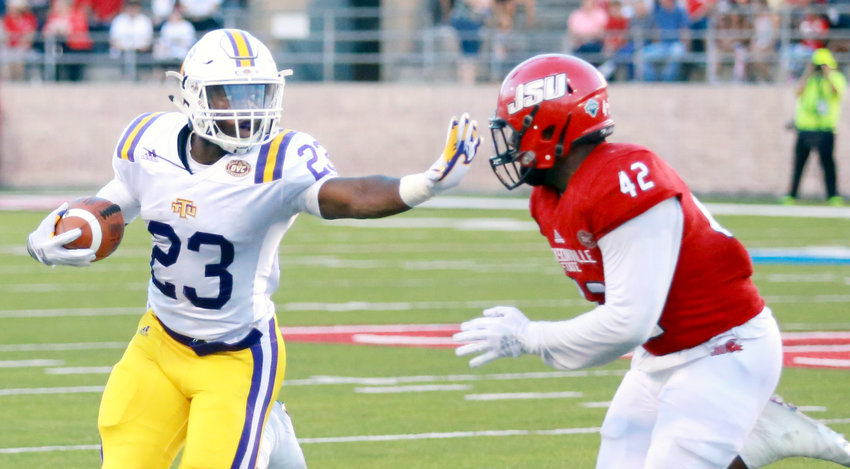 Tennessee Tech tailback Andrew Goldsmith (left) fends off a Jacksonville State University tackler during the Golden Eagles' game Saturday in Jacksonville.