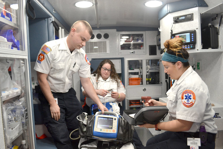 Newly certified Putnam County paramedics, from left, Sam Copeland, Jessica Rogers and Micki Dye check over some of the equipment in the back of an ambulance.