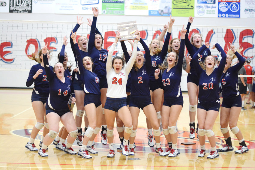 The Cookeville High School volleyball team celebrates after winning the Region 3-AAA Tournament Tuesday night at CHS.