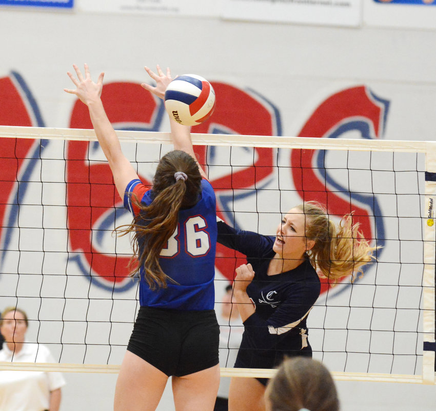 Cookeville's Grace Roberts, right, spikes the ball past a Cleveland blocker during the Lady Cavs' 3-2 win over the Lady Raiders in the Region 3-AAA Championship Tuesday night at CHS.