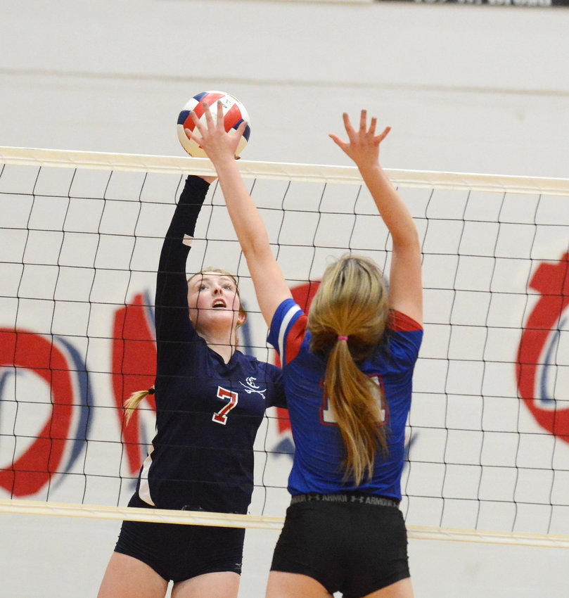 Cookeville's Blake Cherry, left, spikes the ball against a Cleveland blocker during the Lady Cavs' 3-2 win over the Lady Raiders in the Region 3-AAA Championship Tuesday night at CHS.
