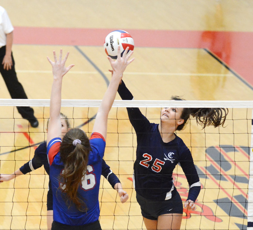 Cookeville's Ruth Ann Ramsey, right, spikes the ball against a Cleveland blocker during the Lady Cavs' 3-2 win over the Lady Raiders in the Region 3-AAA Championship Tuesday night at CHS.