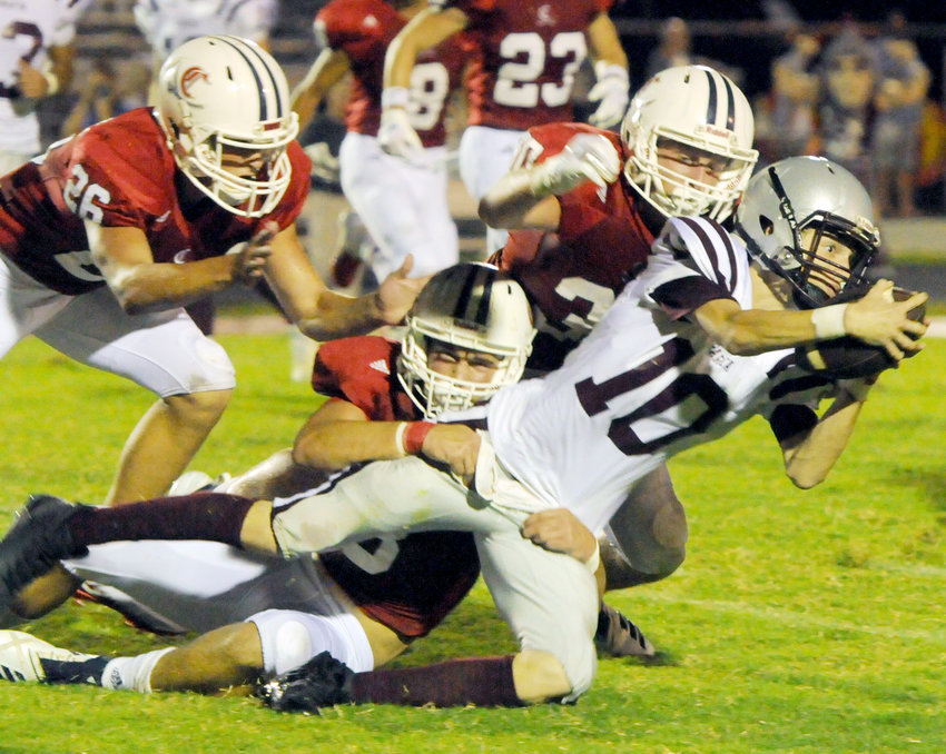 Cookeville's Cooper Norrod (center) and Clay Massengille (30) wrap up White County's Sydreck Leftwich (10) for a tackle during the Cavs' 55-0 win over the Warriors in early September at CHS.