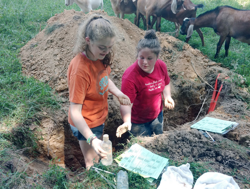 Britta Gaetjens, left, and Cadence Howell work to identify soil characteristics while practicing for the 4-H land contest.