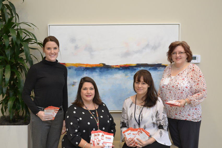 Employees of ATC Automation present gift cards to Susan Simpson, Care Coordinator with the HUGS and CSS Programs. From left are Sydney East, Susan Simpson, Faune Nunnery, and Lorie Judd.