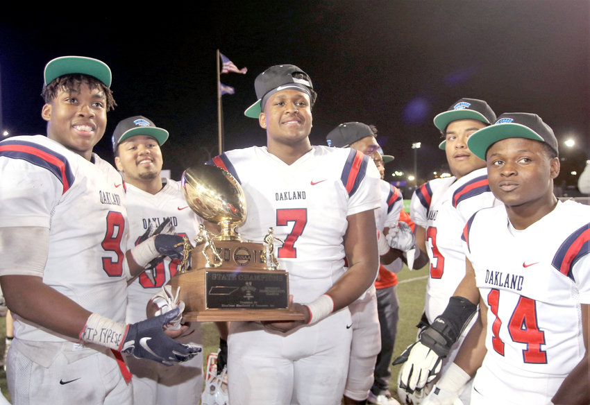 Oakland's Tekoy Randolph, left, and Joesph Anderson hold the championship trophy Thursday after the Pats routed Whitehaven in the 6A title game.