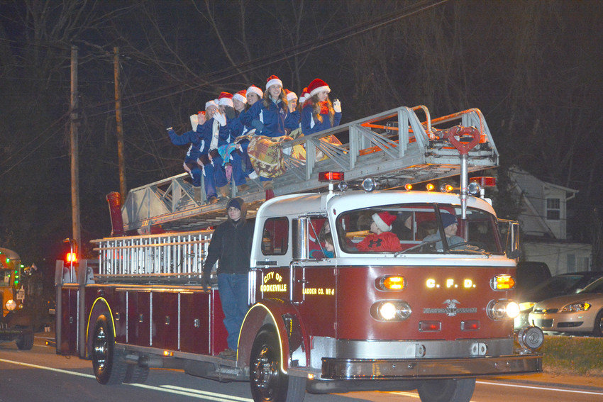 Members of the Cookeville High School Cavalier dance team sit on a fire truck and wave to the crowd at the 2017 Cookeville Christmas parade.