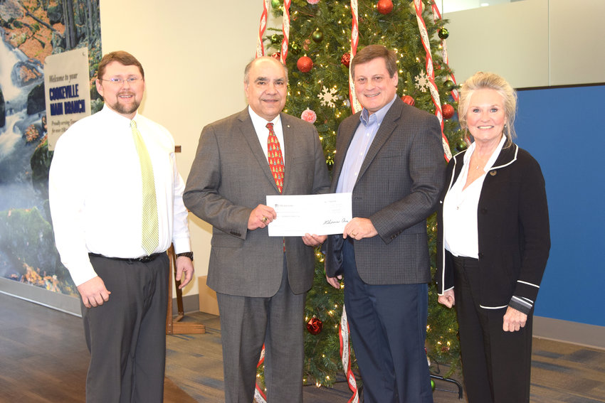 Jeremiah Miller and Nelson Forrester of First Tennessee Bank present a $5,000 check to Mark Hutchins and Cindy Schueman of IMPACT Leadership.