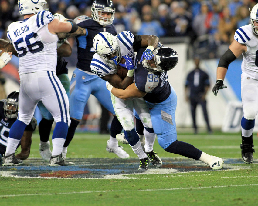 Indianapolis Colts running back Marlon Mack (25) tries to avoid the tackle by Tennessee Titans defensive end Matt Dickerson (92) in the first half of the NFL game at Nissan Stadium in Nashville, Tenn., on Dec. 30, 2018. The Colts win 33-17. (Photo by Matthew Maxey)