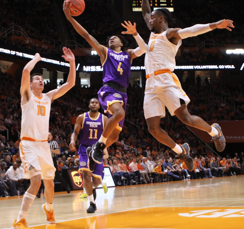 Tennessee Tech's Jr. Clay, left, shoots over a Tennessee defender during a game Saturday in Knoxville.