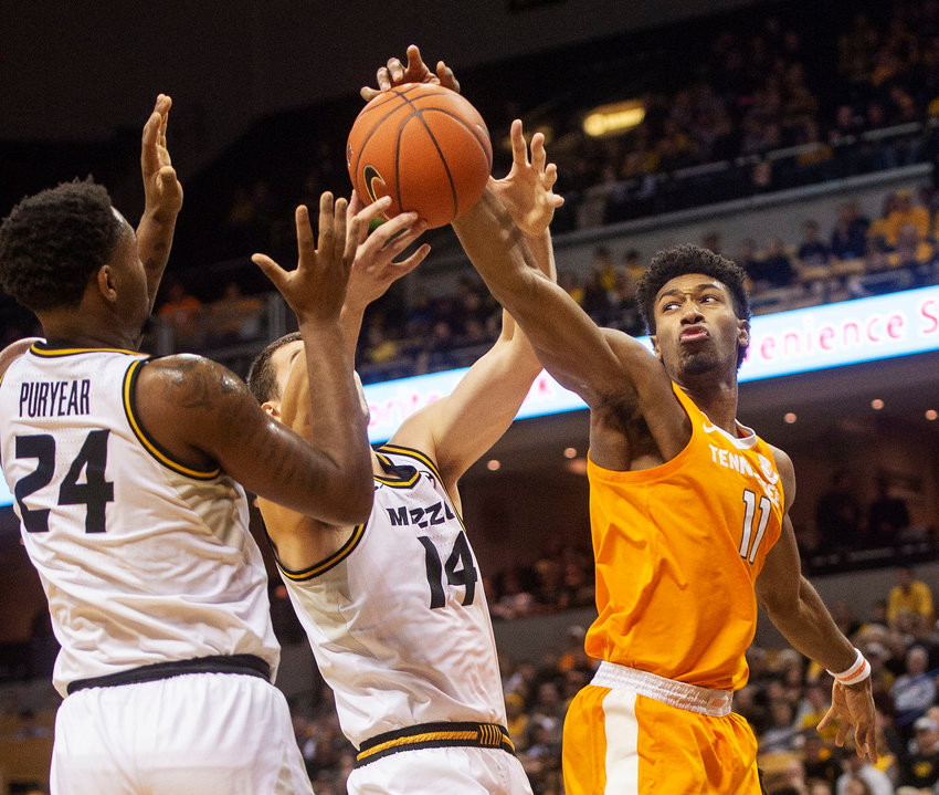 Tennessee's Kyle Alexander, right, Missouri's Kevin Puryear, left, and Reed Nikko, center battle for a rebound during the first half of a game Tuesday in Columbia, Mo.
