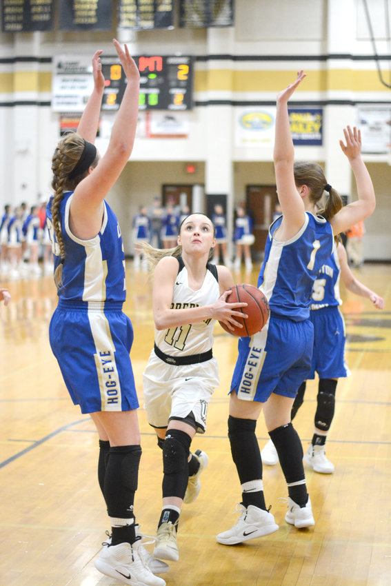 Upperman's Chloe Maynord, center, splits two Livingston Academy defenders during the Lady Bees' 51-25 win over the Lady Wildcats Friday in Baxter.