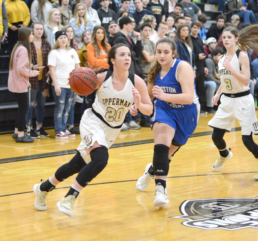 Upperman's Torie Brooks, left, drives past a Livingston Academy defender during the Lady Bees' 51-25 win over the Lady Wildcats Friday in Baxter.