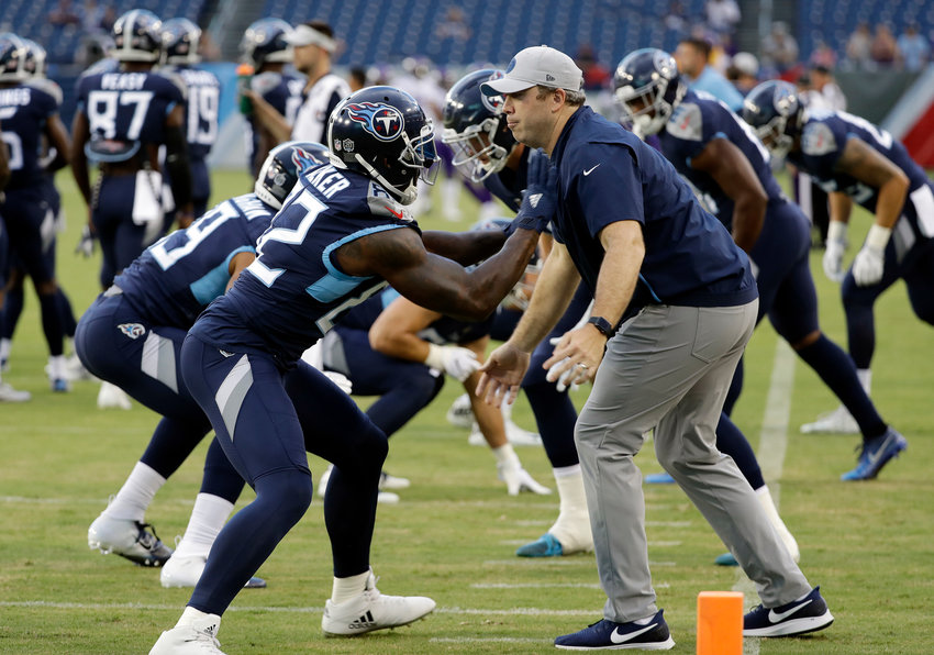 File-This Aug. 30, 2018, file photo shows Tennessee Titans tight ends coach Arthur Smith, right, helping tight end Delanie Walker (82) warm up before a preseason NFL football game in Nashville, Tenn. Mike Vrabel has stayed inside the Tennessee Titans' organization for his new offensive coordinator, promoting tight ends assistant Smith to the job vacated when Matt LaFleur left for the Green Bay Packers' head coaching job.
