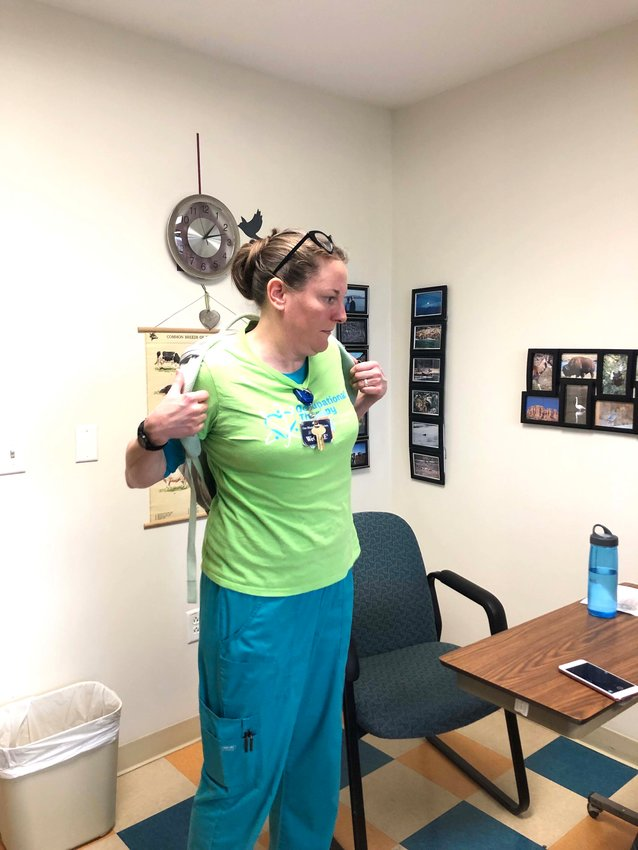 Cookeville Regional Medical Center Occupational Therapist Kelly Hooks demonstrates the best way to put on a backpack.