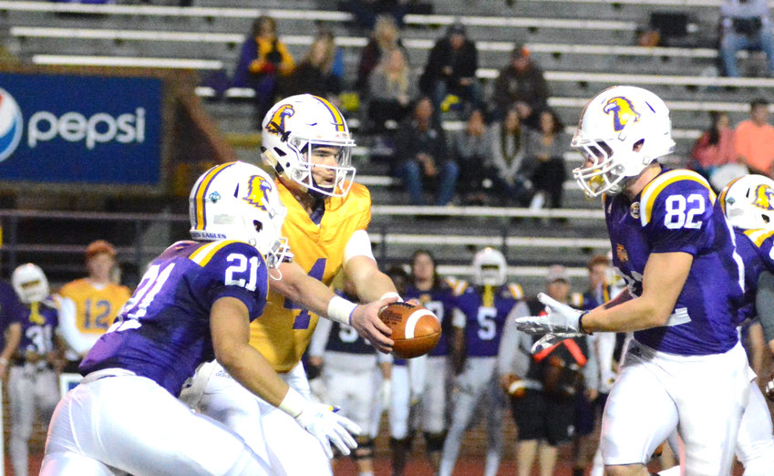 Tennessee Tech quarterback Bailey Fisher prepares to hand off to either David Gist (21) or Seth Huner during the Golden Eagles' spring game Friday night at Tucker Stadium.