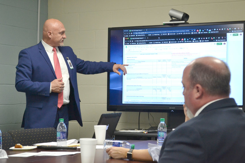 Director of Schools Jerry Boyd, left, goes over preliminary budget numbers during a recent school board work session as Assistant Director Corby King looks on.