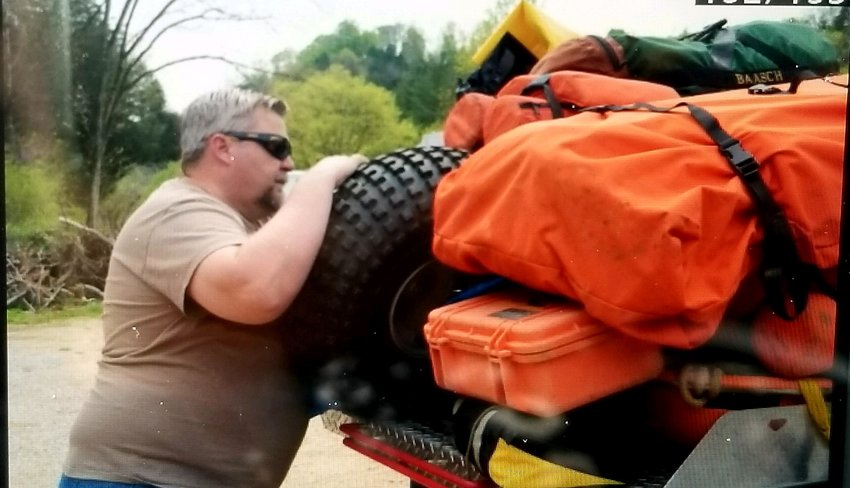 Patrick Martin of the Jackson County Rescue Squad pulls supplies from a truck outside a cave where a British man is stranded Wednesday.