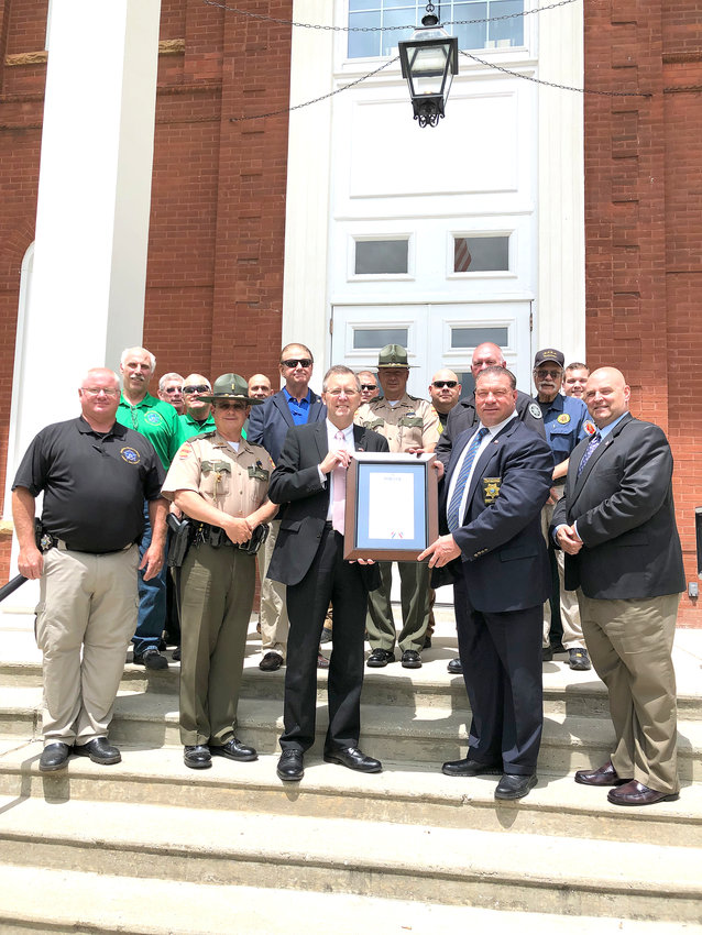 Celebrating National  Police Week, in front, from left, are Stacy Padgett of the Putnam County Sheriff's Office, Jimmy Neal of the Tennessee Highway Patrol, Putnam County Mayor Randy Porter, Sheriff Eddie Farris, Chief Deputy Bob Crabtree; back row, Fred Vondra of the PCSO, Mike Lambert of Tennessee Tech Police, David Hajdik of the National Department of Interior, Rick Baker of PCSO, Bill Loos of the Broward County Sheriff's Office, Dan Gragg of PCSO, Greg Tramel of THP, Steve Elrod of PCSO, Greg Whittaker of PCSO, Dennis Guzlas of Dupage County Sheriff's Office and D.J. Sons of PCSO. National Police Week began Sunday and continues through Saturday.