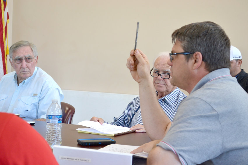 Airport manager Dean Selby, right, makes a point during Tuesday's board meeting as members Charles Green and Hoyt Jones listen.