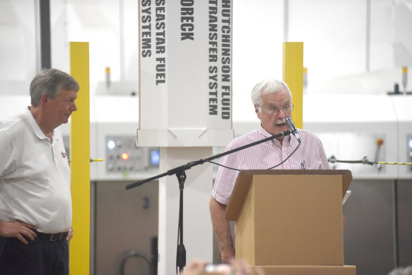 Mayor Bill Wiggins, right, spoke to attendees at Cumberland Container on Friday. Wiggins spoke of how much the company has done for the town in its 50 years of business.