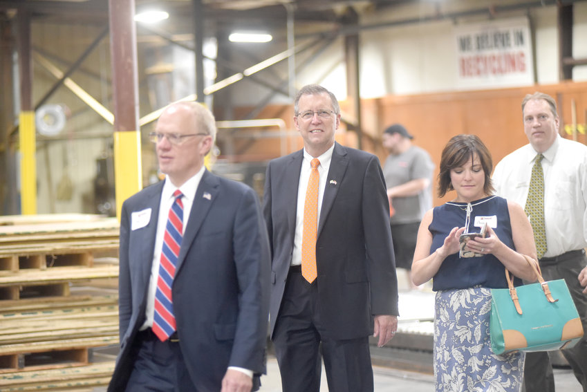 Putnam County Mayor Randy Porter, center, and Congressman John Rose, left, make their way through a tour at Cumberland Container's 50th anniversary ceremony.