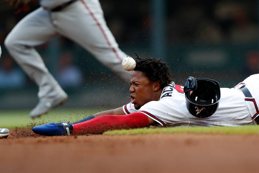 Atlanta Braves' Ronald Acuna Jr. slides ahead of the throw from Washington Nationals catcher Kurt Suzuki as Acuna steals second base during the first inning of a game Thursday in Atlanta.