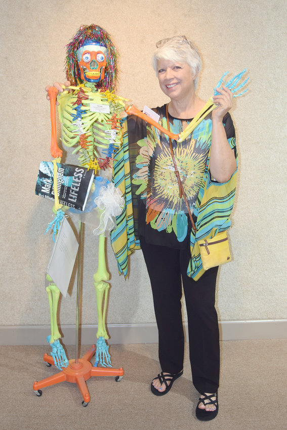 Adrienne Stone poses with her one of her recycled art creations at the Recycled Art Show last year.