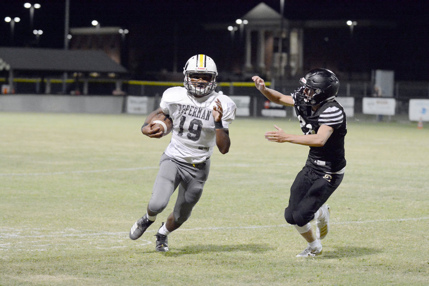 Upperman's Terrence Dedmon, left, runs past a Clay County defender during a scrimmage at UHS on Friday.