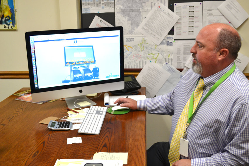 Deputy Director of Schools Corby King looks over the website for a new visitor management system that is expected to be installed in schools next month.