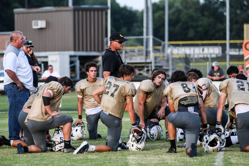 Upperman head coach Adam Caine talks to his team after the scrimmage.