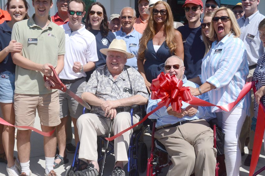 Johnny Coleman, left, and Jack Ray, right, celebrate the Bank of Putnam County new business center ribbon cutting Saturday in downtown Monterey surrounded by citizens and local officials.