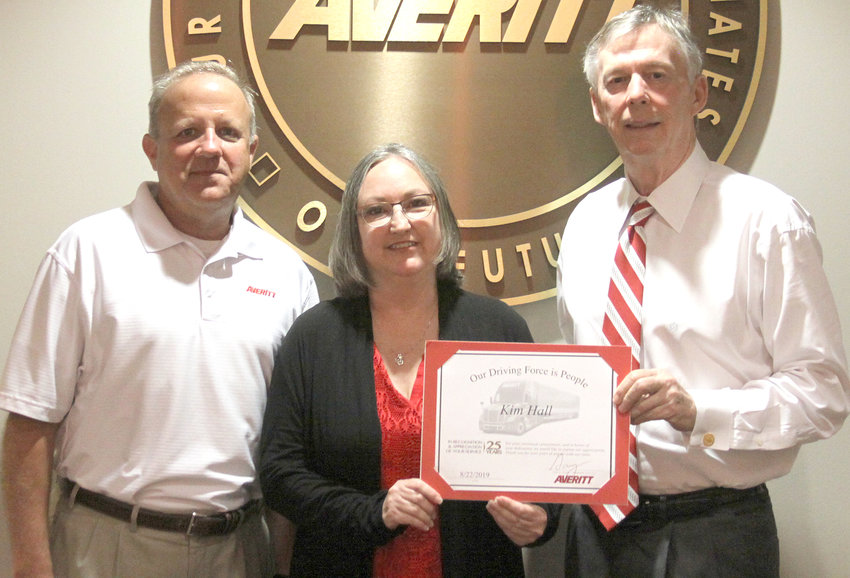 Kim Hall, center, is presented her 25-year service award by director of cargo claim services Gary Whitaker, left, and Averitt chairman and chief executive officer Gary Sasser, right.
