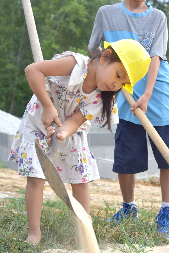 Five-year-old Michelle Bustos shovels sand at the groundbreaking of her family's Habitat for Humanity home in the West End subdivision of Cookeville Tuesday. The Bustos home will be Upper Cumberland Habitat for Humanity's 82nd home and the 12th home built by funds from Cooking on the Square.