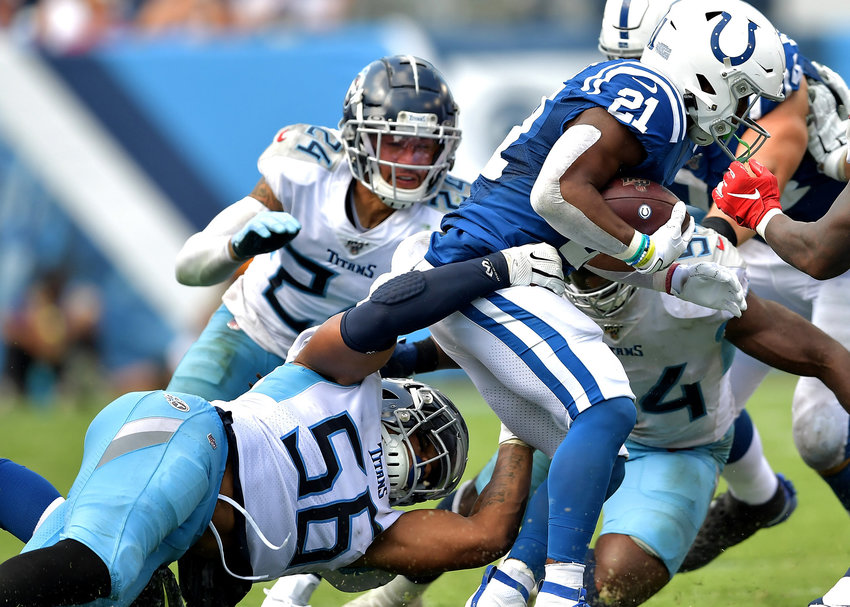 Tennessee Titans linebacker Sharif Finch (56) tries to bring down Indianapolis Colts running back Nyheim Hines (21) during the second half of an NFL game Sept. 15, 2019, at Nissan Stadium in Nashville, Tenn. The Colts beat the Titans 19-17.