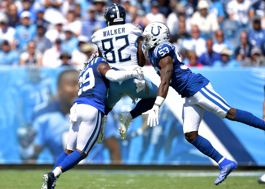 Tennessee Titans tight end Delanie Walker (82) gets hit at the same moment he catches a pass in the first quarter of the NFL game between the Titans and the Indianapolis Colts Sept. 15, 2019, at Nissan Stadium in Nashville, Tenn. The Colts beat the Titans 19-17.