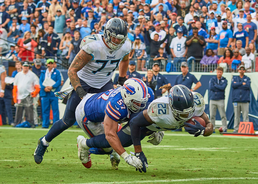 Buffalo Bills outside linebacker Lorenzo Alexander (57) tackles Tennessee Titans running back Derrick Henry (22) in the of an NFL game Sunday, Oct. 6, 2019, at Nissan Stadium in Nashville, Tenn.