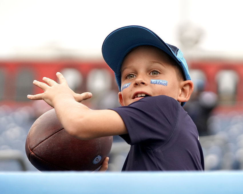A young fan throws a football back to the field prior to the start of the Tampa Bay Buccaneers at Tennessee Titans NFL football game Sunday, Oct. 27, 2019, at Nissan Stadium in Nashville, Tenn.