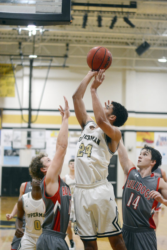 Upperman's Isaiah Allen, center, goes up for a layup during the Bees' 67-35 win over Red Boiling Springs Saturday at UHS.