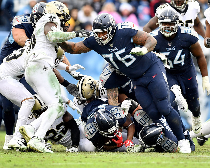 Tennessee Titans running back Dion Lewis (33) goes low for a first down while Titans offensive guard Rodger Saffold (76) offers protection up high in the second quarter of an NFL game against the New Orleans Saints Sunday, Dec. 22, 2019, at Nissan Stadium in Nashville, Tenn.
