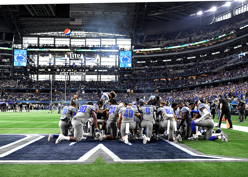 Memphis Tigers players kneel in the end zone prior to the start of the Cotton Bowl NCAA football game between the Tigers and the Penn State Nittany Lions Saturday, Dec. 28, 2019, at AT&T Stadium in Arlington, Texas.