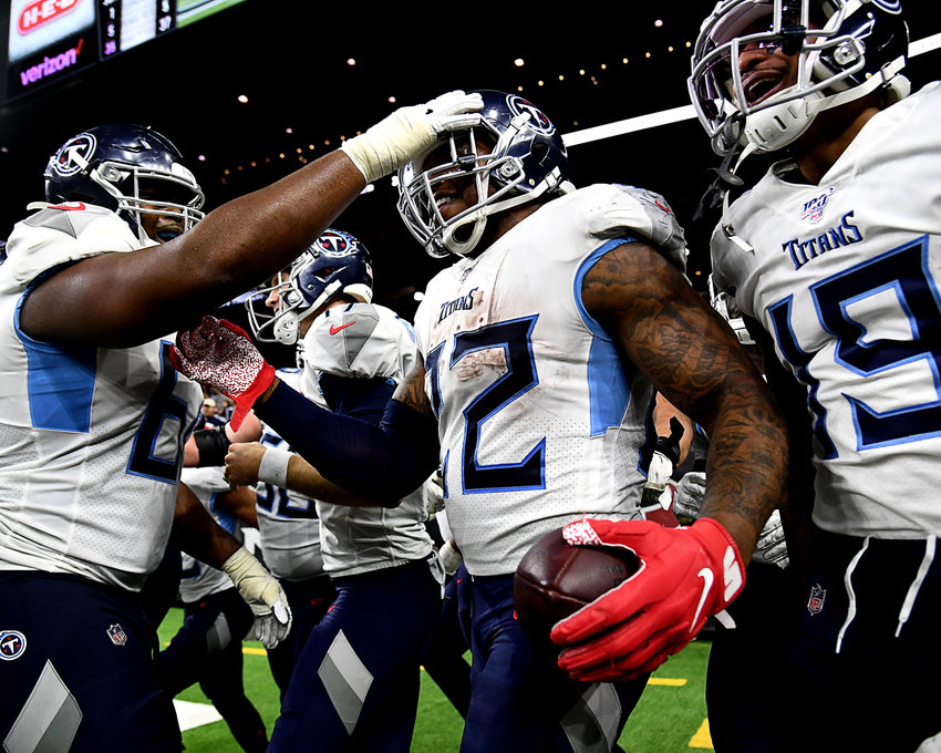 Tennessee Titans running back Derrick Henry (22) celebrates his fourth quarter touchdown with his teammates during an NFL game against the Houston Texans at NRG Stadium in Houston Texas. This 53-yard run also gave Henry, with 1,540 rushing yards for the season, the title of NFL's leading rusher for 2019.