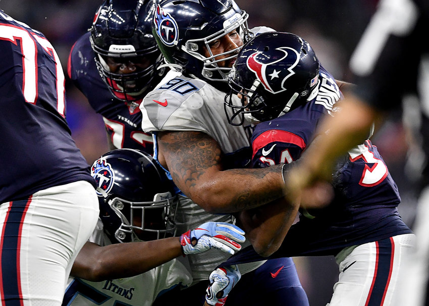 Tennessee Titans defensive end DaQuan Jones (90) wraps up Houston Texans running back Taiwan Jones (34) at the line of scrimmage in the second half of an NFL game Sunday, Dec. 29, 2019, at NRG Stadium in Houston Texas.