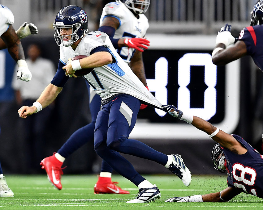 Tennessee Titans quarterback Ryan Tannehill (17) tries to pull away from the tenacious Houston Texans cornerback Vernon III Hargreaves (28) during the first half of an NFL game Sunday, Dec. 29, 2019, at NRG Stadium in Houston Texas.