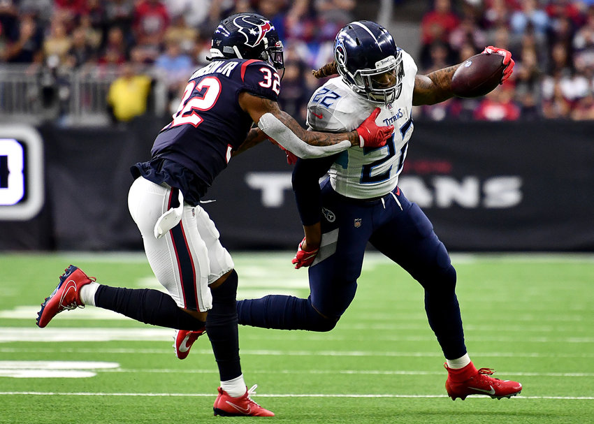 Tennessee Titans running back Derrick Henry (22), on his way to a first down, tries to avoid a tackle by Houston Texans cornerback Lonnie Johnson (32) in the first half of an NFL game Sunday, Dec. 29, 2019, at NRG Stadium in Houston Texas.